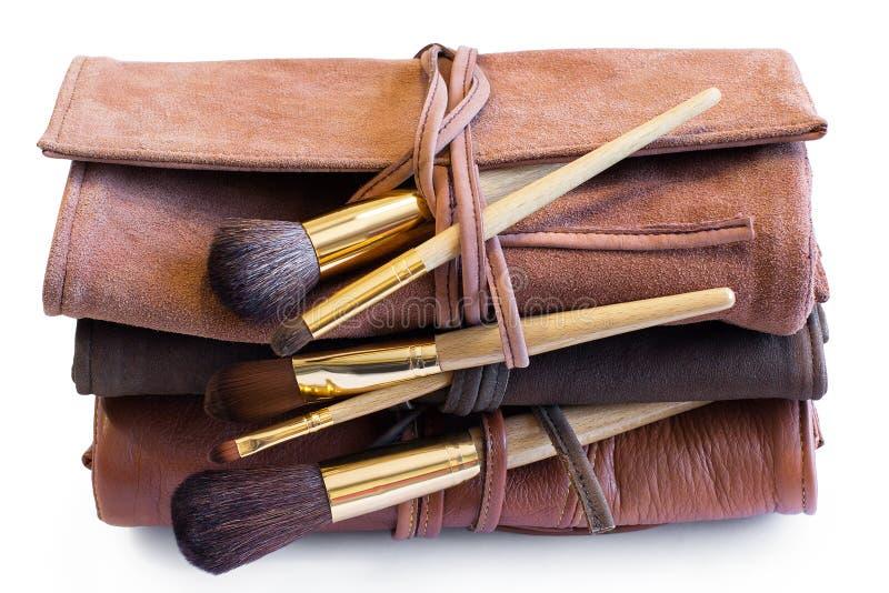 Brosses de maquillage dans coveres en cuir colorés photographie stock libre de droits