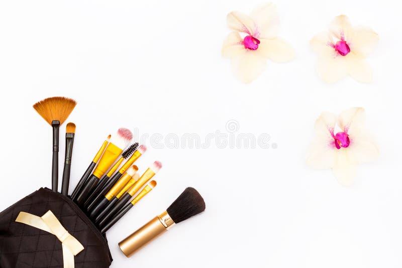 Brosses de maquillage dans le sac noir et fleurs d'orchidée sur le fond blanc Beauté féminine de concept minimal photo stock