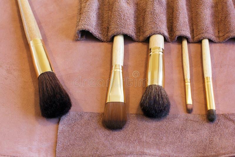 Brosses de maquillage dans une couverture en cuir rose photographie stock