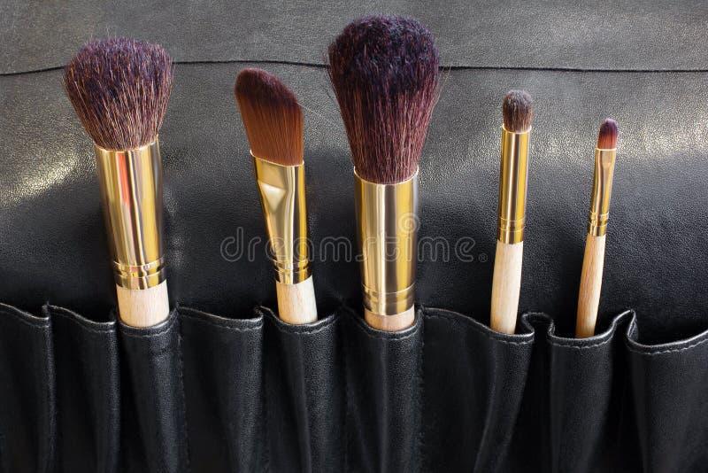 Brosses de maquillage dans une couverture noire image libre de droits