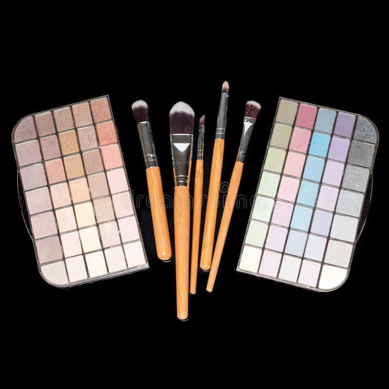 Brosses de maquillage et palette colorée de fards à paupières de maquillage sur le fond noir De mode de femme toujours la vie photo stock