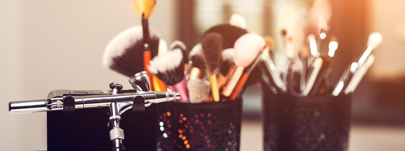 Brosses de maquillage, fin  Aerographe de maquillage et d'autres outils sur la table Produits de maquillage réglés Cosmétiques et photo libre de droits