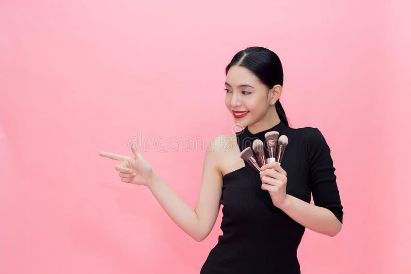 Brosses de transport de maquillage de jeune femme asiatique élégante en main avec l'espace de copie Belle femme à la mode d'isole images stock