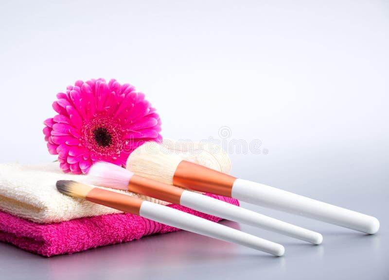Brosses pour le maquillage sur la serviette avec la grande fleur rose photographie stock libre de droits