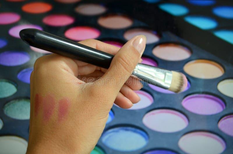 Brosses pour le maquillage sur une palette de fond avec le fard à paupières photo libre de droits