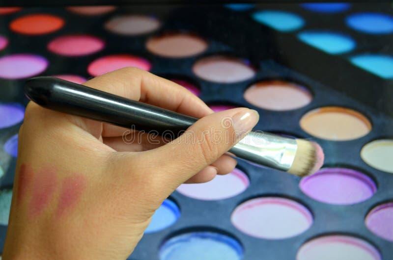 Brosses pour le maquillage sur une palette de fond avec le fard à paupières images stock