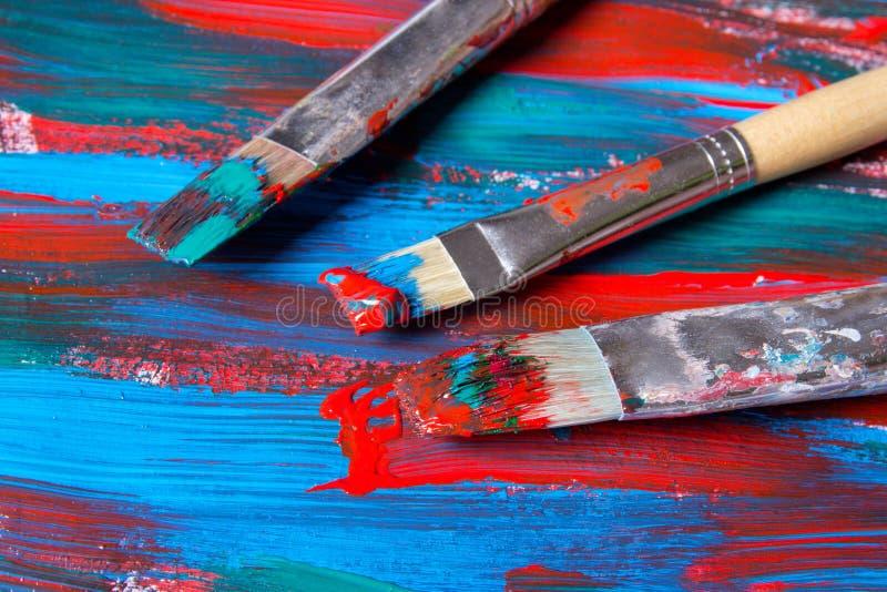 Brosses sur le fond de peinture acrylique avec les courses bleues et rouges image stock