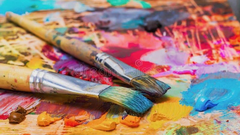 Brosses utilisées sur la palette d'un artiste de la peinture à l'huile colorée photos stock