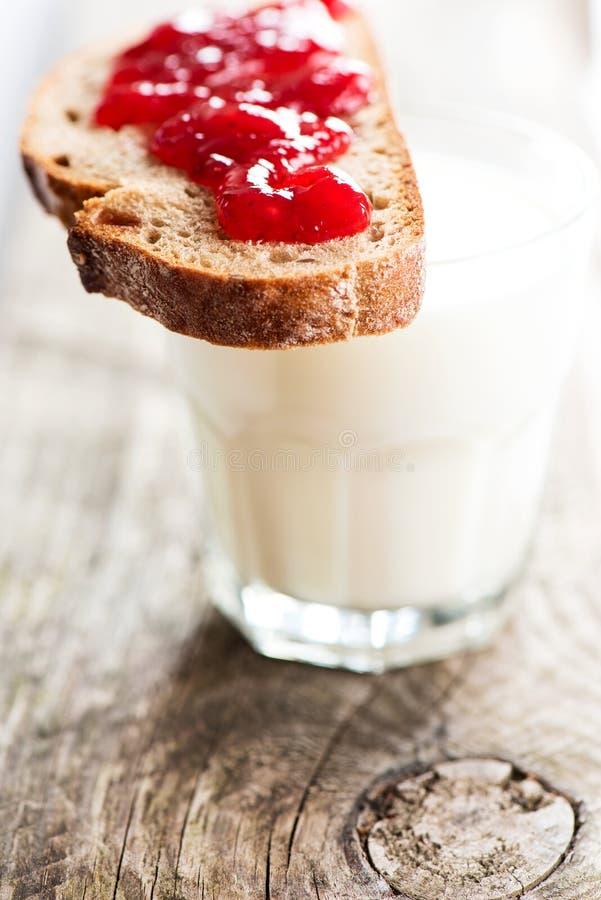 Brot mit Erdbeermarmelade und Glas Milch lizenzfreie stockbilder