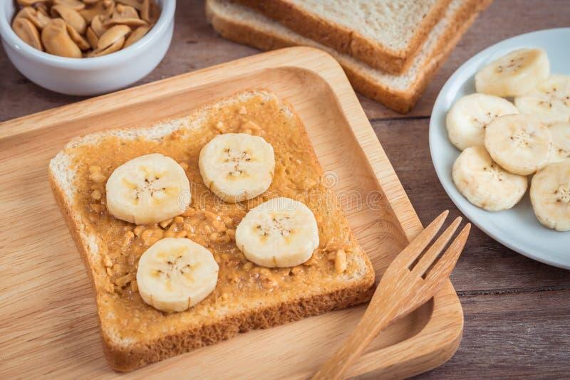 Brot mit Erdnussbutter und Banane auf Platte lizenzfreie stockfotos