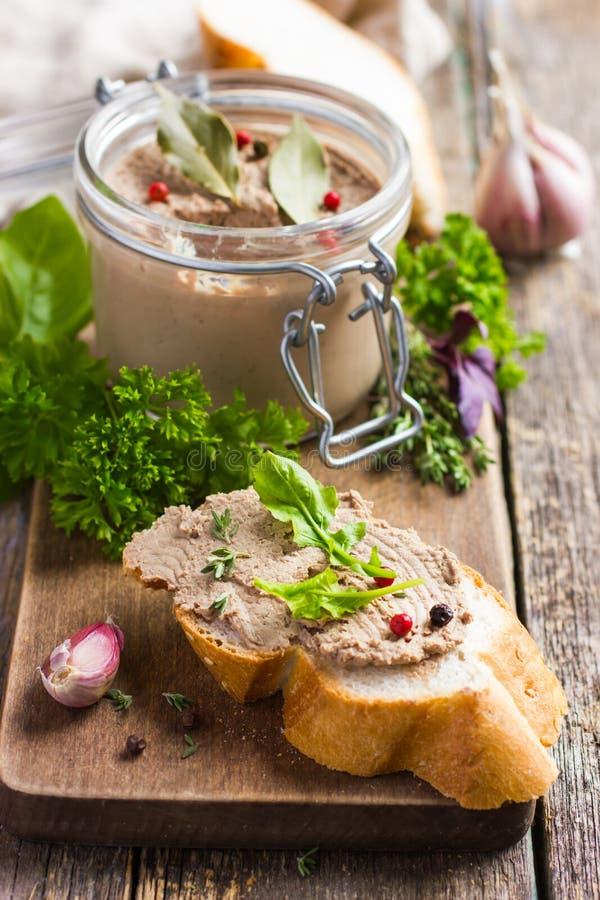 Brot mit hühnerleberpastete auf hölzernem Schneidebrett stockfoto