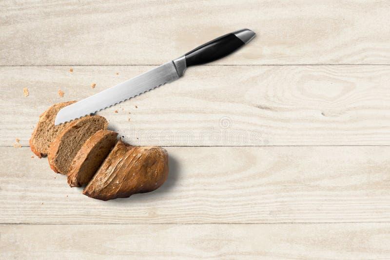Brot mit Messer auf hölzernem Hintergrund lizenzfreie stockfotos