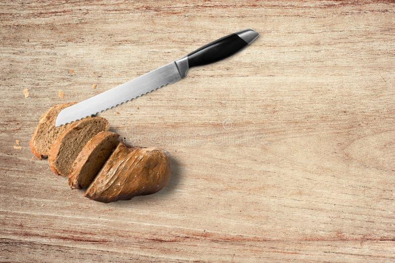 Brot mit Messer auf hölzernem Hintergrund auf Wei? stockfotos