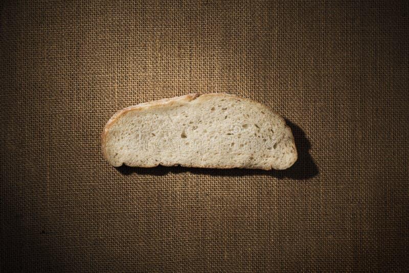 Brot-Scheiben-Stück über Leinwand-Gewebe, Hinterpauschen-Mahlzeit über Sack-Stoff lizenzfreie stockfotos