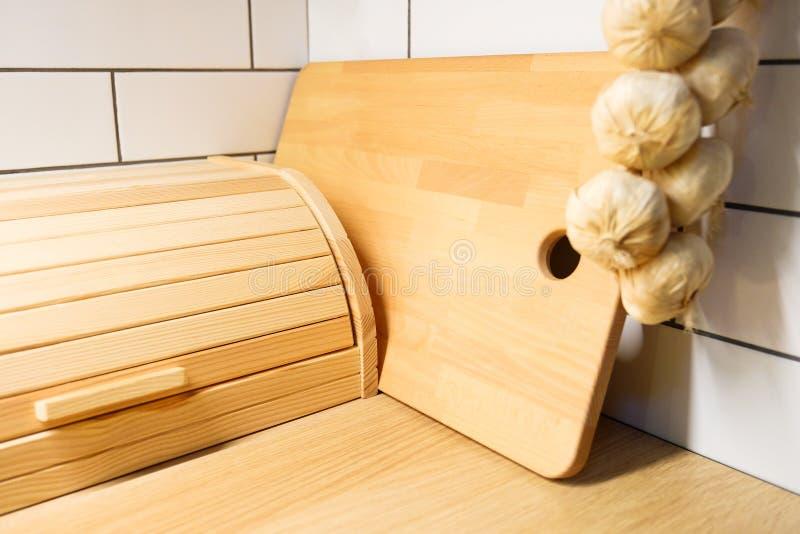 Brotdose Ansicht der Küchenarbeitsplatte mit Schneidebrett, an die Wand einige Köpfe des Knoblauchs hängend lizenzfreies stockbild
