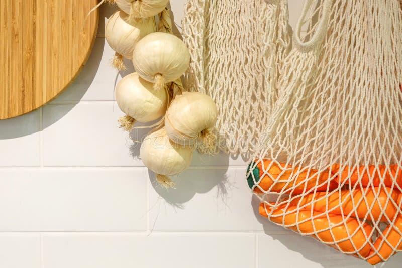 Brotdose Ansicht der Küchenarbeitsplatte mit Schneidebrett, an die Wand einige Köpfe des Knoblauchs hängend stockfotografie