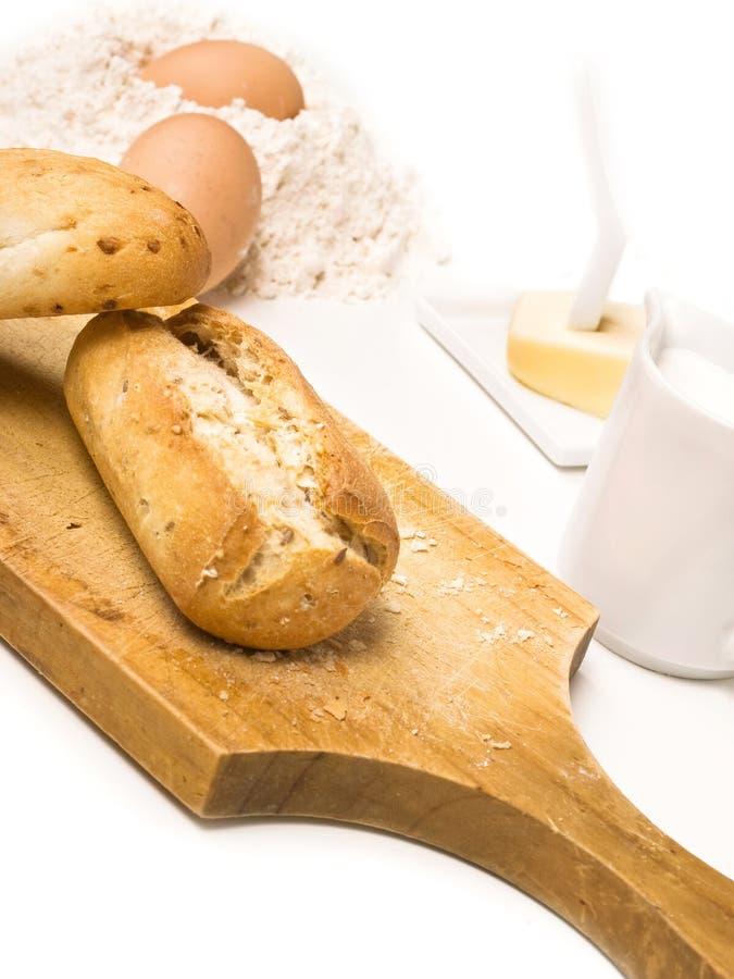 Brote auf einem Küchenbrett mit Butter, Eiern und Milch lizenzfreie stockfotografie