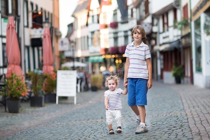 Brotehr and his baby sister in a historical city centre. Brotehr and his little baby sister walking and playing in a historical city centre stock photo