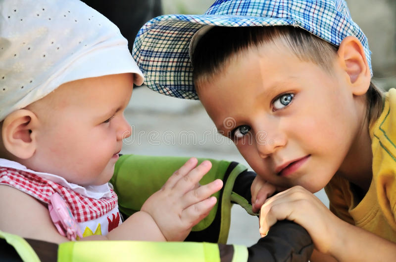 Brother and Baby Sister. Young boy holding carriage of his baby sister royalty free stock images