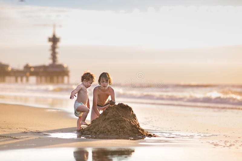 Brother and baby sister building sand castle. Brother and baby sister building a sand castle having fun together stock photo