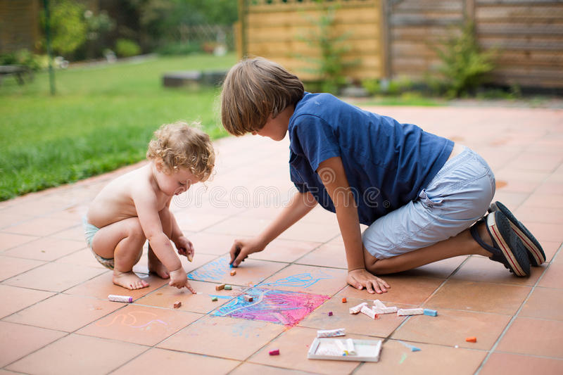 Brother and baby sister painting with colorful chalk. Brother and his baby sister playing together in the backyard painting with colorful chalk stock images