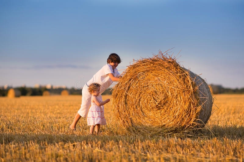 Brother and baby sister pushing hay bales in a field. At sunset stock photo