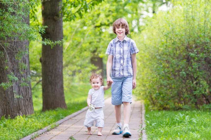 Brother and baby sister walking in the park. Brother and baby sister walking in the summer park stock images