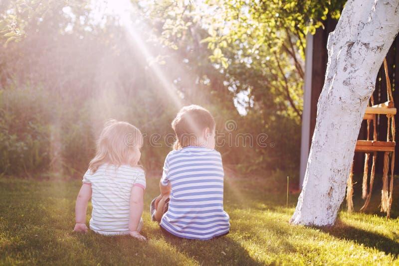 Brother con su pequeña hermana al aire libre detrás dos niños se sientan en la hierba imagenes de archivo