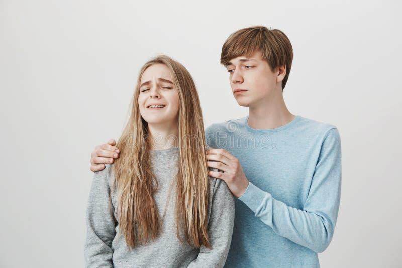 Brother estará siempre allí para la hermana Dos hermanos que se colocan sobre la pared gris después de noticias impactantes de la foto de archivo
