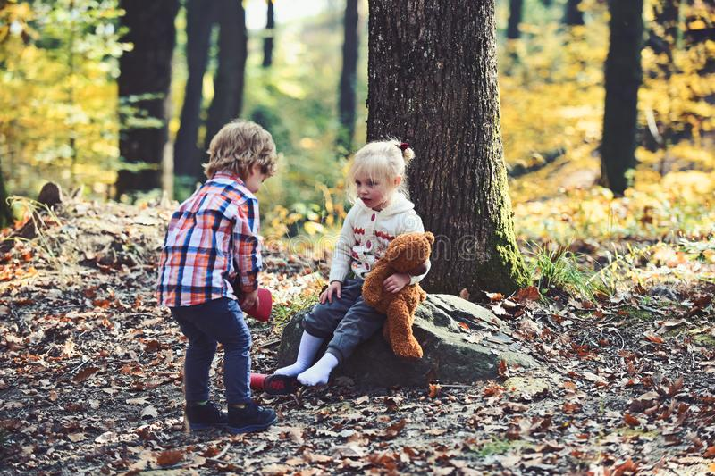 Brother help sister to put red boots. Little boy put shoes on girl feet. Helping hand concept. Children getting ready. For walk in autumn forest. Childhood royalty free stock photography