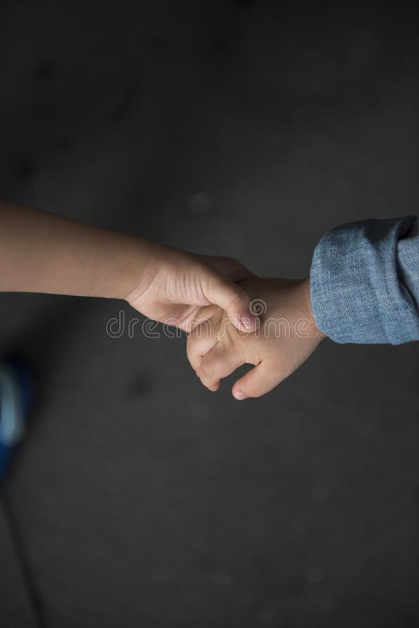Brother holding his younger brother hand with care and love. royalty free stock photography
