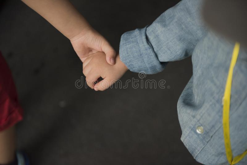 Brother holding his younger brother hand with care and love. stock photography