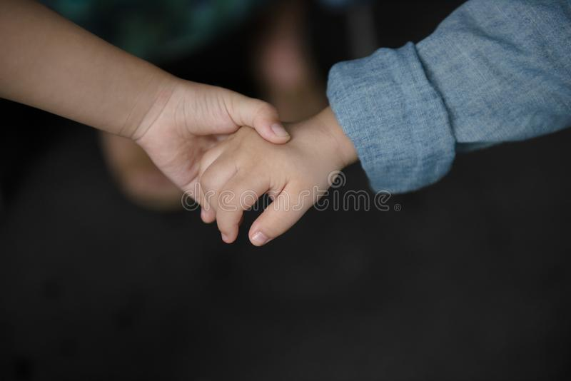 Brother holding his younger brother hand with care and love. royalty free stock image
