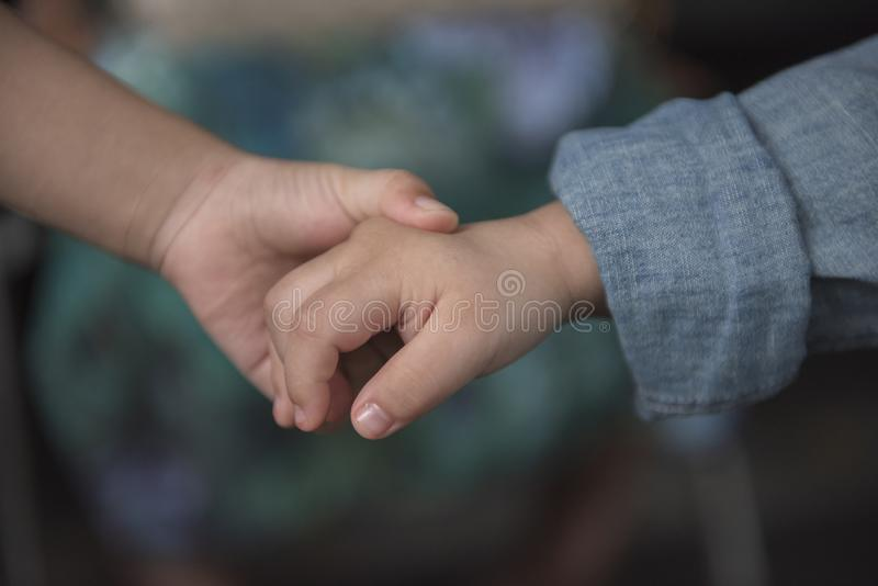 Brother holding his younger brother hand with care and love. royalty free stock photo