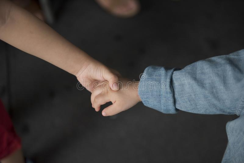 Brother holding his younger brother hand with care and love. stock image