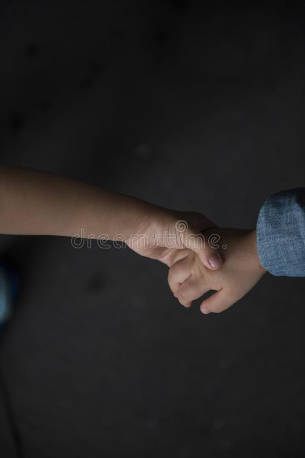 Brother holding his younger brother hand with care and love. stock photo