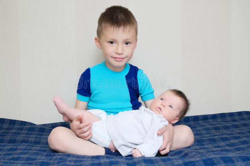 Brother holding little newborn sister lying on his legs at home stock photos