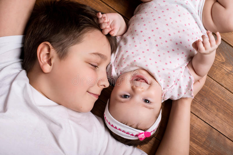 Brother hugging his newborn sister. View from above.  stock image