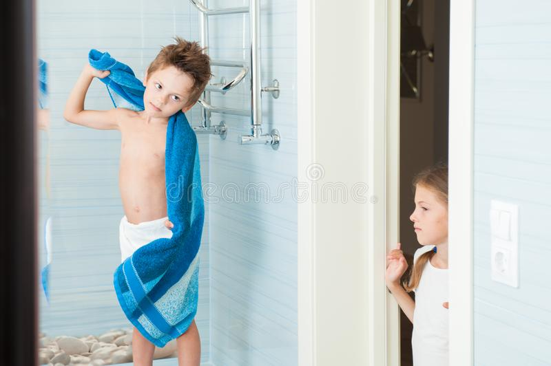 Brother kid with towel and sister girl standing in door in bathroom in morning royalty free stock photography