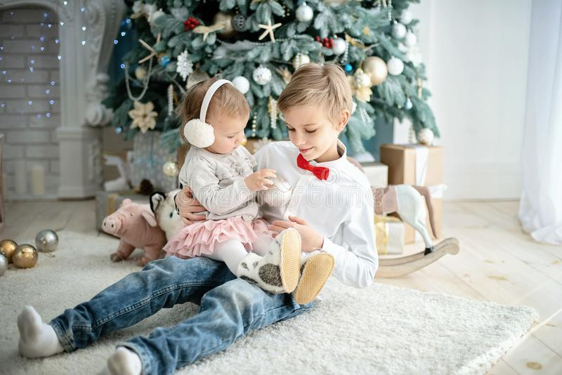 Brother and little sister under Christmas tree. Smiling boy giving Christmas gift to girl. Family holiday stock photography