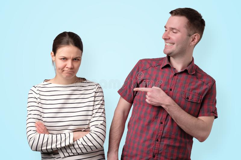Brother pointing on his sister laughing on her problems. stock photos