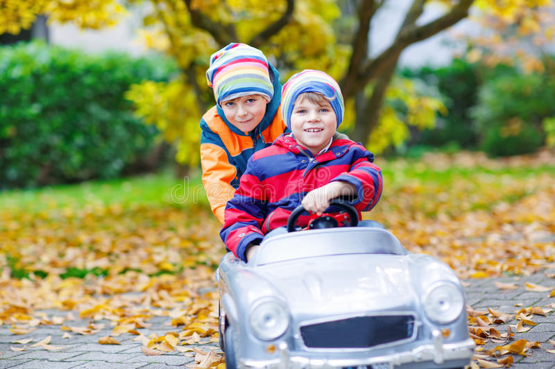 Brother pushing car for child. Happiness, fun, leisure in fall park. Two happy twins kids boys having fun and playing with big old toy car in autumn garden royalty free stock photo