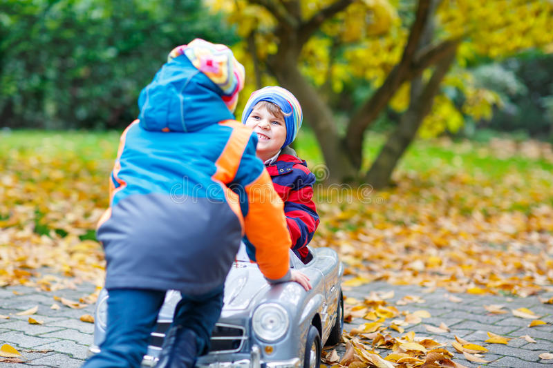 Brother pushing car for child. Happiness, fun, leisure in fall park. Two happy twins kids boys having fun and playing with big old toy car in autumn garden stock photography