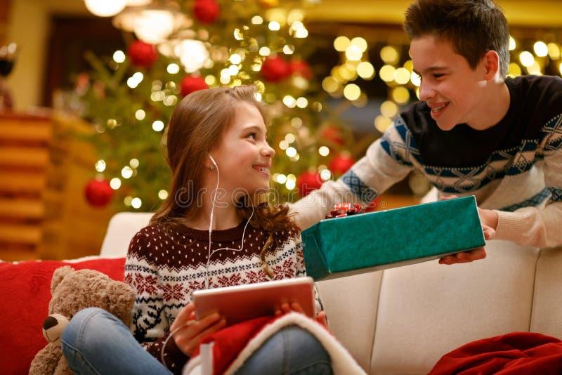 Brother que da el regalo de Navidad en caja a su hermana fotografía de archivo libre de regalías