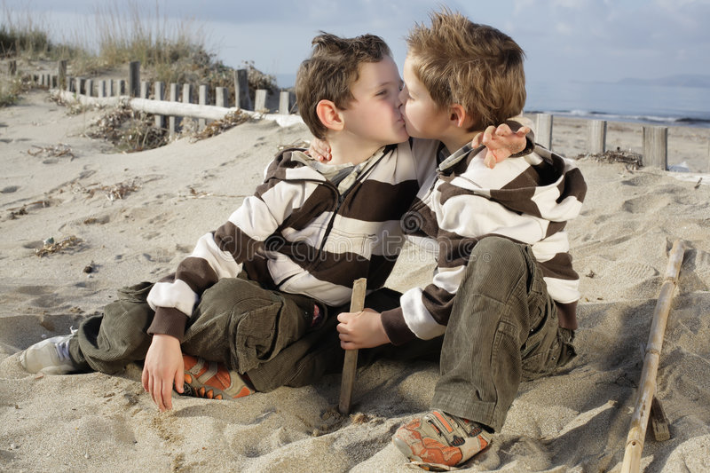 Brother's kiss. Two little boys kissing sitting on the beach royalty free stock image