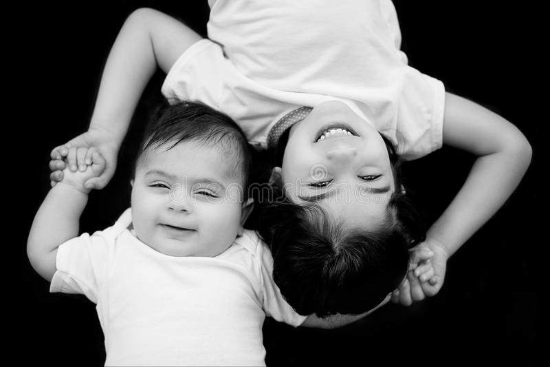 Brother and sister. Baby brother and sister laying down and holding hands royalty free stock images