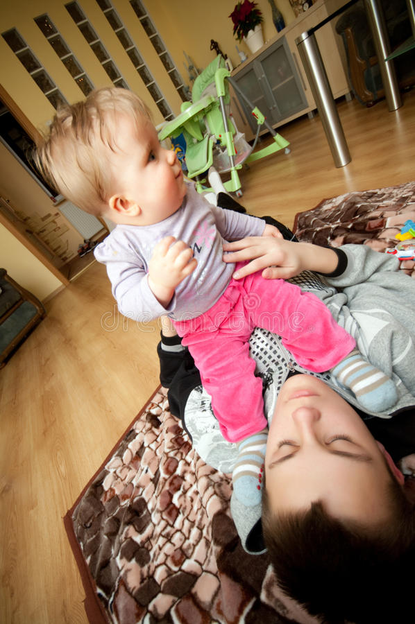 Brother and sister. Teenage brother plays with his baby sister at home royalty free stock image
