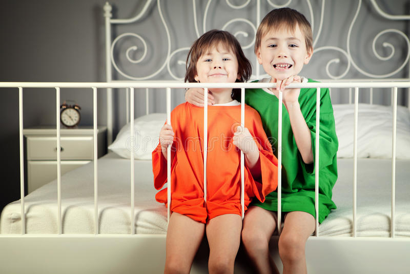 Brother and Sister. In their parents' bed stock photography