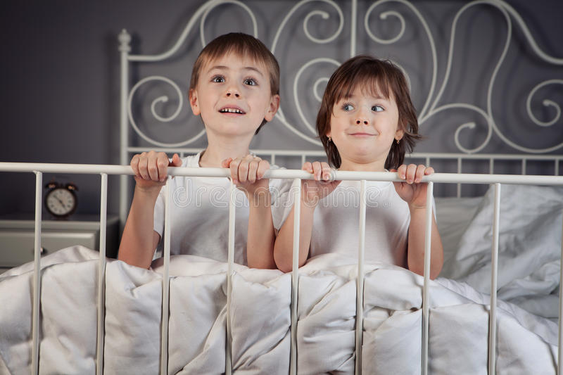 Brother and Sister. In their parents' bed royalty free stock photography