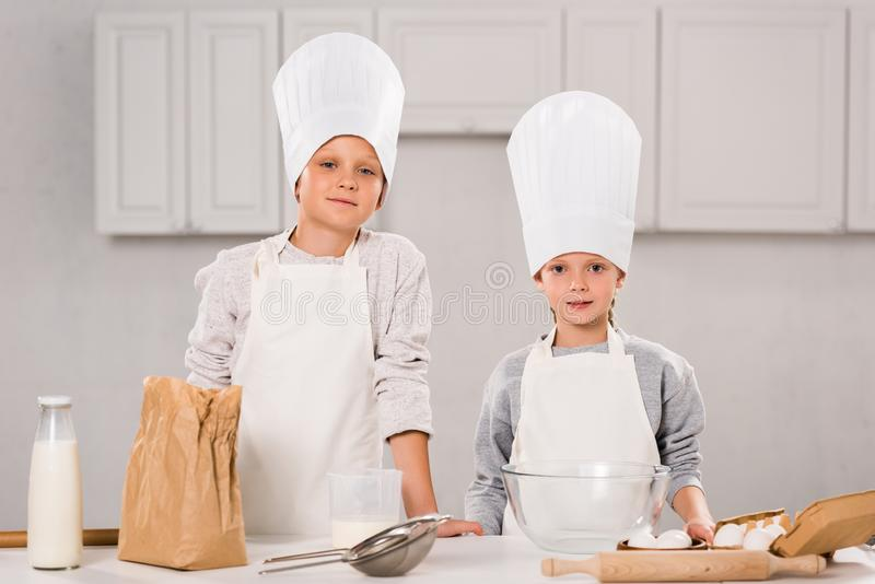 Brother and sister in aprons and chef hats looking at camera. In kitchen royalty free stock images